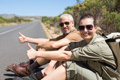 Hitch hiking couple sitting on the side of the road smiling at camera Royalty Free Stock Photography