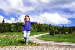 Hitch-hiking by cute little  girl Royalty Free Stock Photo