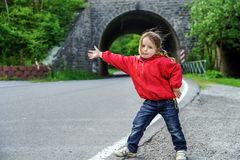 Hitch-hiking by little girl Royalty Free Stock Photo