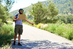 Hitch-hiking traveler with a blank cardboard sign Royalty Free Stock Image