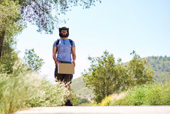 Hitch-hiking traveler with a blank cardboard sign Stock Image