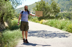 Hitch-hiking traveler with a blank cardboard sign Royalty Free Stock Photo