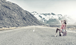 Hitch hiking traveling. Young retro woman waiting on road with her vintage baggage Royalty Free Stock Photography