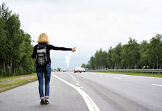 HITCH HIKING. Woman hitch hiking at the road in cloudy day Stock Image