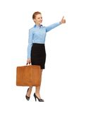 Hitch-hiking woman with suitcase Stock Images