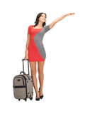 Hitch-hiking woman with suitcase royalty free stock image