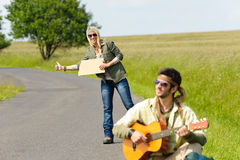 Hitch-hiking young couple backpack asphalt road Stock Photo
