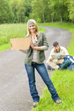 Hitch-hiking young couple backpack asphalt road Royalty Free Stock Image