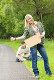 Hitch-hiking young couple backpack asphalt road Stock Images
