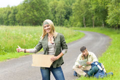 Hitch-hiking young couple backpack asphalt road Royalty Free Stock Photo