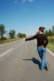 Hitchake 08. Young girl hitchhiking on the road Royalty Free Stock Photography