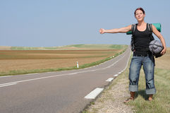 Hitchhike. Hitchhiking girl on a lonely country road Royalty Free Stock Image