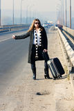 Hitchhike. Woman with a suitcase hitching near a road Royalty Free Stock Photos