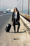 Hitchhike. Woman with a suitcase standing near a road Stock Photo