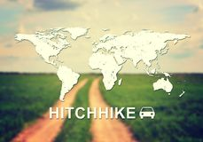 Hitchhike header. Contoured map of world continents with inscription Hitchhike and related symbol. Blurred photo of unsurfaced road in field as backdrop Royalty Free Stock Image