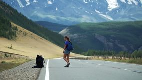 Hitchhiker γυναικών είναι μακροχρόνια αναμονή για τα αυτοκίνητα και κλωτσά ένα σακίδιο πλάτης σε έναν δρόμο βουνών Υπάρχουν βουνά φιλμ μικρού μήκους