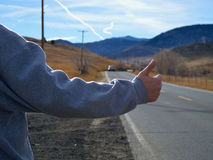 Hitchhiker on deserted highway Stock Photography
