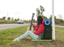 Hitchhiker with guitar Royalty Free Stock Images