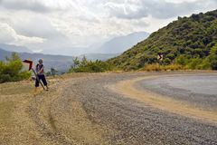 Hitchhiker installs sign on dangerous road bend. Young man in shorts, a bachpacker or hitchhiker, installs a road safety sign on dangerous turn of serpentine Stock Images