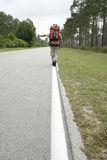 Hitchhiker. On a lonely road Royalty Free Stock Photo