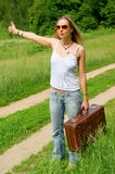 Hitchhiker with old suitcase Royalty Free Stock Photos