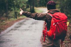 Hitchhiker with red backpack alone on the road. Travel Lifestyle concept rear view Royalty Free Stock Image