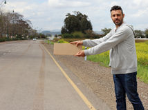 Hitchhiker on the road. Bum stand on the side of the road wating for a car to hitchhike him Royalty Free Stock Images