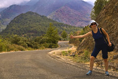 Hitchhiker on the road in mountains. Young woman in shorts and with bag stands at the mountain serpentine road and thumbs a lift Royalty Free Stock Image