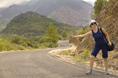Hitchhiker on the road in mountains. Young woman in shorts and with bag stands at the mountain serpentine road and thumbs a lift Royalty Free Stock Photos