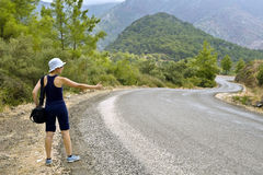Hitchhiker on the road in mountains. Young woman in shorts and with bag stands at the mountain serpentine road and thumbs a lift Royalty Free Stock Photography