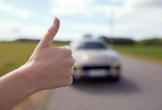 Hitchhiker stopping car with thumbs up hand sign Royalty Free Stock Photo
