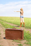 Hitchhiker with a suitcase Stock Image