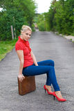 Hitchhiker with suitcase. Blond hitchhiker with suitcase on the road Royalty Free Stock Image