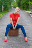 Hitchhiker with suitcase. Blond hitchhiker with suitcase on the road Stock Photos