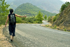 Hitchhiker thumbing a lift. Young man in shorts and with bachpack walks along the mountain serpentine road and thumbs a lift Stock Image