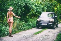 Hitchhiker woman in bikini on the road Royalty Free Stock Photos