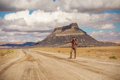 Hitchhiker woman walking on a road in USA royalty free stock photos