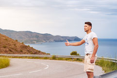 Hitchhiker young man. Hitchhiker young man, hitchhiking on a rural road hitchhiking on the background of the road, blue see and sky, suny day Royalty Free Stock Photos
