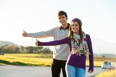 Hitchhikers adolescentes ao longo da estrada secundária. Fotografia de Stock