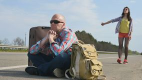 Hitchhikers near the road. Father and daughter catching a car hitchhiking near the road. The man sits on ground between backpack and suitcase. Pretty girl stands stock video footage