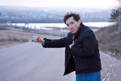 Hitchhiking. A young man hitchhiking car on the road Royalty Free Stock Images