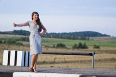 Hitchhiking. Young girl is stopping the car  on the countryside bus stop Stock Image