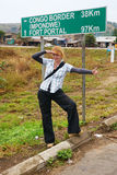 Hitchhiking blonde girl in Africa. Extreme tourism. Pretty young woman tourist hitchhiking along a road near Congo border signpost in central Africa, equator Stock Image