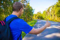 Hitchhiking concept - back view of man standing on forest road. Hitchhiking concept - back view of man with backpack standing on forest road Royalty Free Stock Images