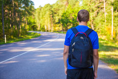 Hitchhiking concept - back view of man walking on forest road. Hitchhiking concept - back view of man with backpack walking on forest road Stock Photo