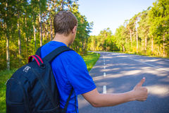 Hitchhiking concept - man standing on forest road. Hitchhiking concept - man with backpack standing on forest road Stock Photo