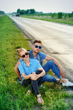 Hitchhiking couple. Happy young people sitting by the highway Stock Photos