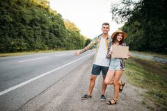 Hitchhiking couple holds blank cardboard. With copy space. Hitchhike adventure of young men and woman. Happy hitchhikers on road Stock Image
