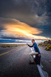 Hitchhiking on a desert road at sunset. Young woman hitchhiking with a suitcase on an empty road at sunset Royalty Free Stock Photo