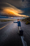 Hitchhiking on a desert road at sunset. Young woman hitchhiking with a suitcase on an empty road at sunset Royalty Free Stock Photography